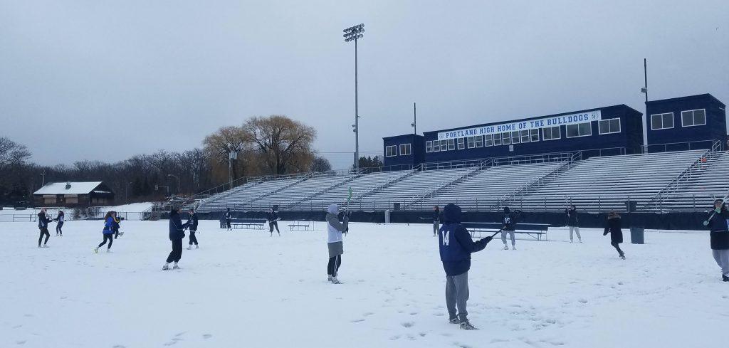Lacrosse team practice in the snow.